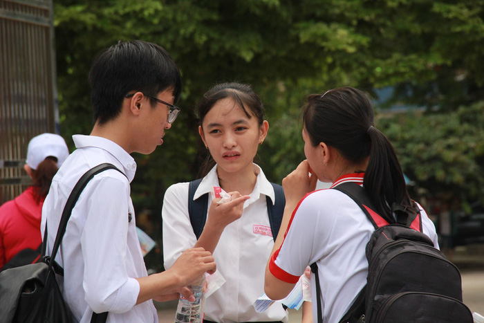 Nhóm ba thí sinh trao đổi với khuôn mặt buồn thiu sau khi thi môn Toán. Ảnh: TTO