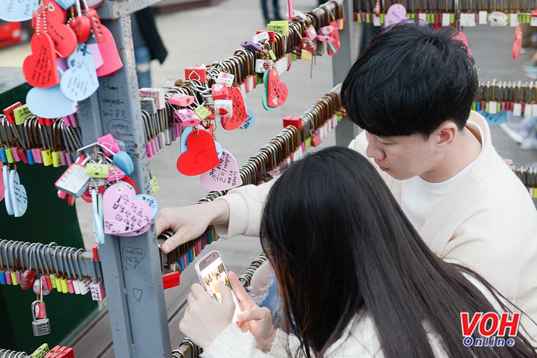 Một đôi tình nhân người Hàn Quốc cùng gắn ổ khóa tình yêu vào hàng rào sắt dưới chân tháp truyền hình Namsan.