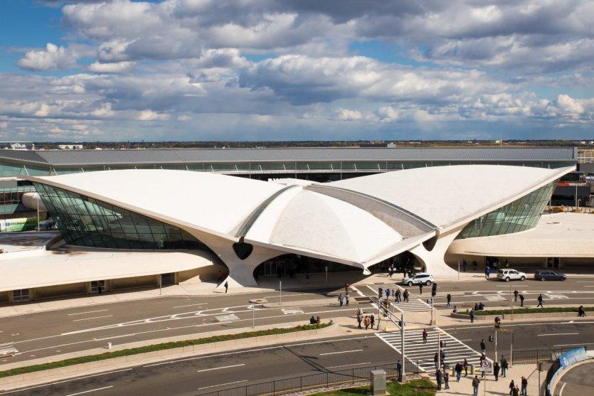 """5. Sân bay JFK - New York, Hoa Kỳ: Sân bay JFK nằm trong bảng xếp hạng các sân bay tốt nhất thế giới. Đặc biệt, nhà ga số 5, nhà ga trung tâm bay Hàng không xuyên thế giới (TWA), mang hình dáng một con chim khổng lồ đang sải cánh bay hướng lên trời. Nhà ga được thiết kế năm 1962 bởi kiến trúc sư Eero Saarinen và được xem là """"công trình lịch sử"""" như một biểu tượng của New York lúc bấy giờ. Một trong những cửa ngõ hàng đầu, vô cùng hiện đại nhưng đáng tiếc là sau những cuộc tấn công ngày 11/9/2001 thì nhà ga đã bị bỏ hoang 15 năm qua. Tuy vậy, chúng ta sẽ được nhìn ngắm TWA lần nữa trong sự biến hóa từ nhà ga thành khách sạn."""