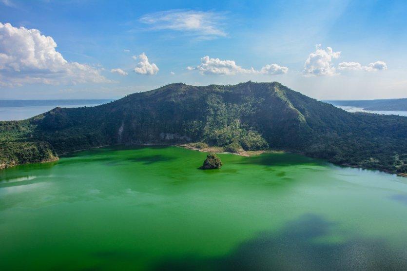 """8. Taal, Philippines: Núi lửa Taal nằm trên hòn đảo Luzon, cách thủ đô Manila 60 km. Mọi người đừng bị đánh lừa bởi hình dáng """"mỏng manh"""" của ngọn núi, nhưng đây lại là ngọn núi lửa hoạt động mạnh đứng thứ 2 Philippines và được xem là có mức sát thương nhất đất nước này qua các đợt phun trào dữ dội khiến 5.000 - 6.000 người thiệt mạng. Tuy nhiên, ngọn núi Taal giữa hồ nước lớn tạo nên một bức tranh thiên nhiên nước non đặc sắc mà những ai bước chân đến đất nước Philippines không thể bỏ lỡ."""