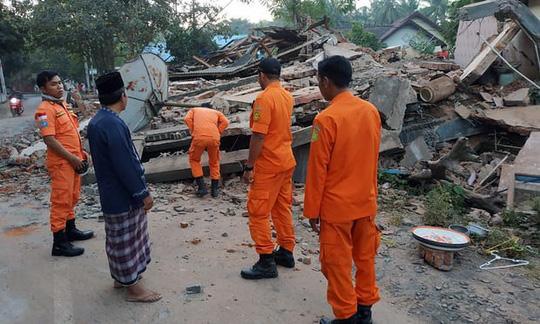 Nhân viên cứu hộ kiểm tra các ngôi nhà đổ sập sau trận động đất ở Bắc Lombok. Ảnh: EPA